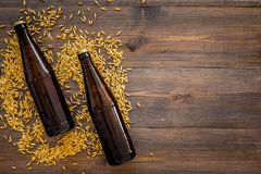 Grains of malting barley near beer bottle on wooden background top view copyspace. Grains of malting barley near beer bottle on wooden background top view Royalty Free Stock Photos