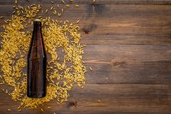 Grains of malting barley near beer bottle on wooden background top view copyspace. Grains of malting barley near beer bottle on wooden background top view Royalty Free Stock Image