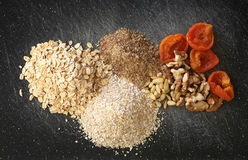Grains, nuts, dry fruits on a black chopping board stock image