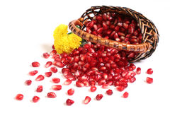 Grains of a pomegranate, flowers in a basket. Royalty Free Stock Image