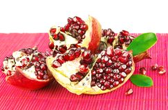 Grains of pomegranate with leaves on mat Stock Photo