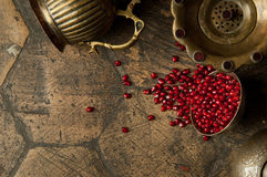 Grains of pomegranate on old paving stones Stock Photos