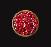 Grains of a pomegranate in woooden bowl isolated on black background. Top view. Royalty Free Stock Photography