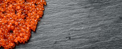 Grains of red caviar. On black rustic background royalty free stock images