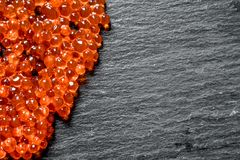 Grains of red caviar. On black rustic background stock photography