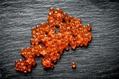Grains of red caviar. On black rustic background royalty free stock photography