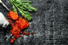 Grains of red caviar with salt and dill. On black rustic background royalty free stock image