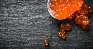 Grains of red caviar on a spoon. On black rustic background royalty free stock images