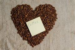 Grains renversés de plan rapproché parfumé de café Cadre de photo, fond Coeur des grains de café Une déclaration de l'amour Images libres de droits