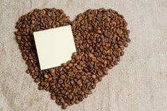 Grains renversés de plan rapproché parfumé de café Cadre de photo, fond Coeur des grains de café Une déclaration de l'amour Image libre de droits