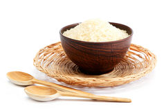 Grains of rice in a bowl and wooden spoon. Stock Image