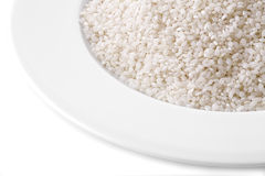 Grains of rice on white plate Stock Images