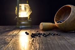 Grains of roasted coffee, kerosene lamp and mortar Royalty Free Stock Photos