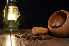 Grains of roasted coffee, kerosene lamp and mortar Stock Images
