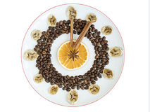 Grains of roasted coffee, mugs of dried orange and banana, cinnamon stick, anise star lie on a porcelain plate in the form of a cl Royalty Free Stock Photo