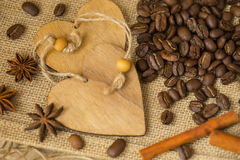 Grains of roasted coffee on sackcloth background with decorative wooden hearts. Coffee background with copy space for Royalty Free Stock Images