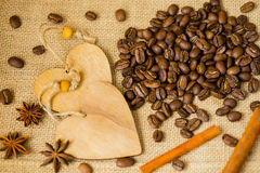Grains of roasted coffee on sackcloth background with decorative wooden hearts. For creative concepts for any day or Stock Image