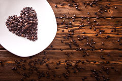 Grains roasted coffee in the shape of heart on  white plate Royalty Free Stock Photo