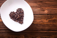 Grains roasted coffee in the shape of heart on  white plate Stock Photos
