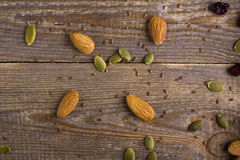 Grains, seeds, and the seeds scattered on wooden background. Almonds, pumpkin seeds, linseed and cranberry on plank background Royalty Free Stock Photography