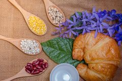 Grains in a wooden spoon and put on sackcloth croissants. Royalty Free Stock Photo