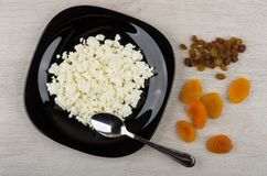 Grainy cottage cheese in plate, teaspoon, scattered dried aprico. Grainy cottage cheese in black plate, teaspoon, scattered dried apricots and raisin on wooden Royalty Free Stock Photo