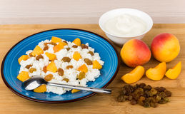 Grainy curd with peaches and raisins, bowl with sour cream Stock Image