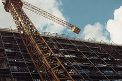 Grainy vintage construction site of a building with crane backgr Royalty Free Stock Photography
