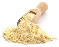 Gram flour. In a wooden scoop over white background stock image