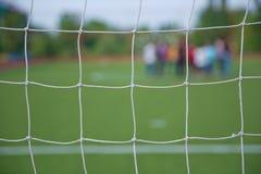Grama artificial de Mini Football Goal On An Pena defocused dos jogadores do futebol no campo pequeno, campo de bola de Futsal no Imagens de Stock Royalty Free
