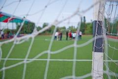 Grama artificial de Mini Football Goal On An Pena defocused dos jogadores do futebol no campo pequeno, campo de bola de Futsal no Fotos de Stock