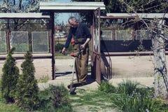 Grama caucasiano do corte do homem em seu jardim da frente Lugar da vila Fotos de Stock Royalty Free