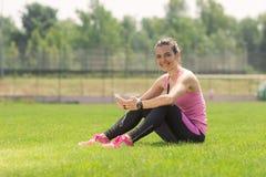 Grama da menina do atleta usando os fones de ouvido do smartphone que sentam a grama Foto de Stock