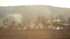 Grama de queimadura perto da floresta com lotes do fumo ao lado das casas de madeira no por do sol contra a montanha e o sol bril filme