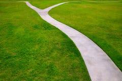 A grama do gramado do jardim com maneiras de umas duas opções detour Fotos de Stock