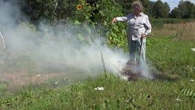 Grama e recusa superiores da queimadura da mulher do camponês no fogo no prado no quintal da vila rural 4K filme