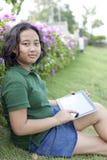 A grama verde do sittingon da menina com computador marca à disposição Fotografia de Stock Royalty Free