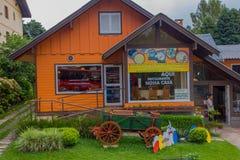 GRAMADO BRASILIEN - MAJ 06, 2016: det trevliga orange huset med något växter och en vagn på beklär trädgården Royaltyfri Bild