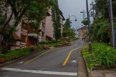 GRAMADO BRASILIEN - MAJ 06, 2016: trevlig ojämn gata med många växter och träd i trottoarerna Arkivbilder