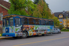 GRAMADO, BRAZIL - MAY 06, 2016: nice and colorfull bus parked in the street in front of some trees.  Royalty Free Stock Images