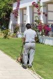 Gramado de sega do homem em um jardim do hotel Imagens de Stock Royalty Free