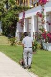 Gramado de sega do homem em um jardim do hotel Imagem de Stock
