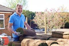 Gramado novo de Laying Turf For do jardineiro de paisagem imagens de stock royalty free