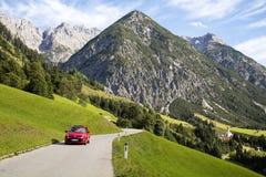 Gramais Österrike, 12 September 2015: Röd bilkörning på den alpina vägen, Gramais, österrikare Arkivfoton