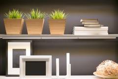Grame a imagem de madeira do vaso, do livro e do quadro na prateleira home Fotografia de Stock