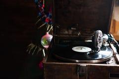 Grammofon som spelar ett rekord med vinyl på bakgrundsgarneringar, locket, träd och ljusa ljus Arkivfoto