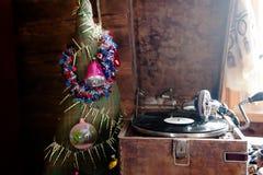 Grammofon som spelar ett rekord med vinyl på bakgrundsgarneringar, locket, träd och ljusa ljus Arkivbilder