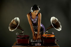 Gramophone dj. Sexy young woman djs using two retro antique gramophones. cool and quirky concept clip Stock Images