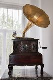 Gramophone in front of a window. In vintage interior stock photography