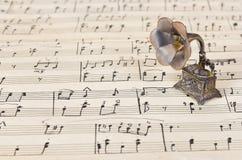 Gramophone on old sheet music. Retro art background Royalty Free Stock Photos